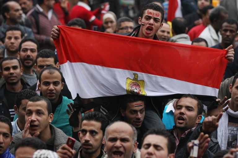 <p>A man holds Egypt's flag in Tahrir Square as people gather for the first anniversary of the revolution on Jan. 25 in Cairo, Egypt.</p>