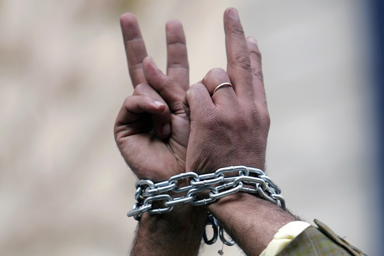 <p>An Egyptian human right activist with chained hands gives the V-sign for victory during a protest against torture in police stations in Cairo in 2007.</p>