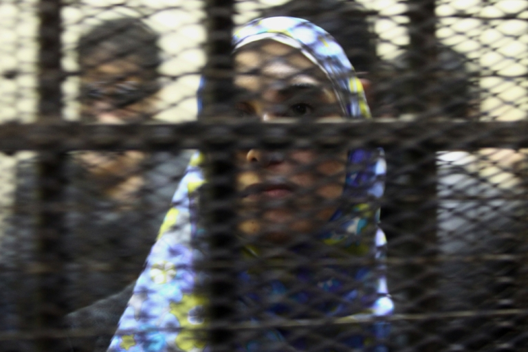 <p>One of fourteen Egyptian activists who worked in Egypt with civil society groups stands inside a cage during their trial in Cairo Sunday.</p>