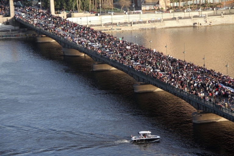 <p>Thousands of Egyptian protesters walk along the Kasr al-Nile bridge as they attend a rally in Cairo on Jan. 27, 2012 to demand democratic change, a year after the uprising that toppled Hosni Mubarak.</p>