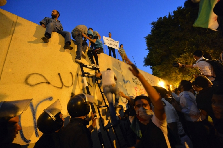 <p>Egyptian riot police stand guard as protesters climb down from the wall of the US embassy in Cairo on September 11, 2012 during a demonstration against a film deemed offensive to Islam. Thousands of Egyptian demonstrators angered by the film produced by expatriate members of Egypt's Christian minority living in the United States tore down the US flag during the protest at the embassy.</p>