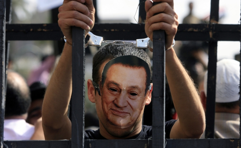<p>An Egyptian protester wearing the mask of ousted Egyptian president Hosni Mubarak stands with handcuffs inside a makeshift prison cell at Cairo's Tahrir Square on April 8, 2011 during a demonstration attended by tens of thousands of Egyptians.</p>