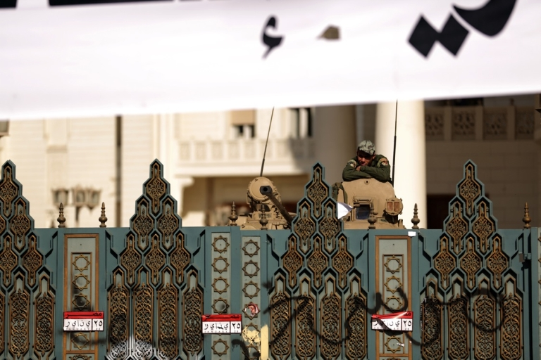 <p>An Egyptian Republican Guard rests on his tank behind the gates of the presidential palace in Cairo on December 8, 2012. Egypt's military thrust itself into the political crisis by demanding dialogue and warning it would not permit events to take a 'disastrous' turn, amid protests against President Mohamed Morsi's expanded powers and efforts to push through a new constitution.</p>
