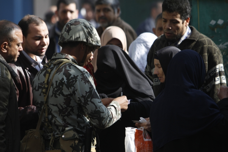 <p>An Egyptian soldier checks the ID card of a Niqab-clad woman at the entrance of a polling station in Qaliubia, some 40 kms north of Cairo, on January 4, 2012 as Egyptians headed to the polls again in the final round of a phased election to choose the first parliament since a popular uprising toppled Hosni Mubarak in February. AFP PHOTO/MOHAMMED ABED</p>