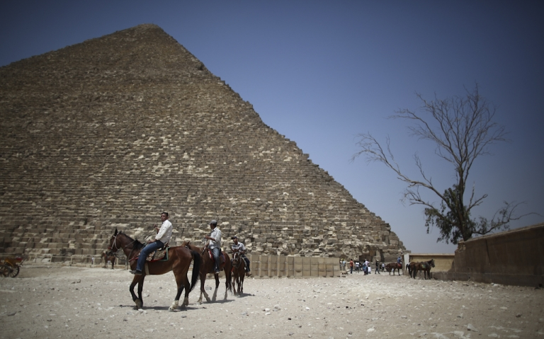 <p>Horses for tourists pass near the Great Pyramid of Cheops in Giza, Egypt. Cheops, the largest Great Pyramid, was closed November 11, 2011 because of rumors that spiritual groups would try to hold rituals and ceremonies there, at 11:11 on 11/11/11.</p>
