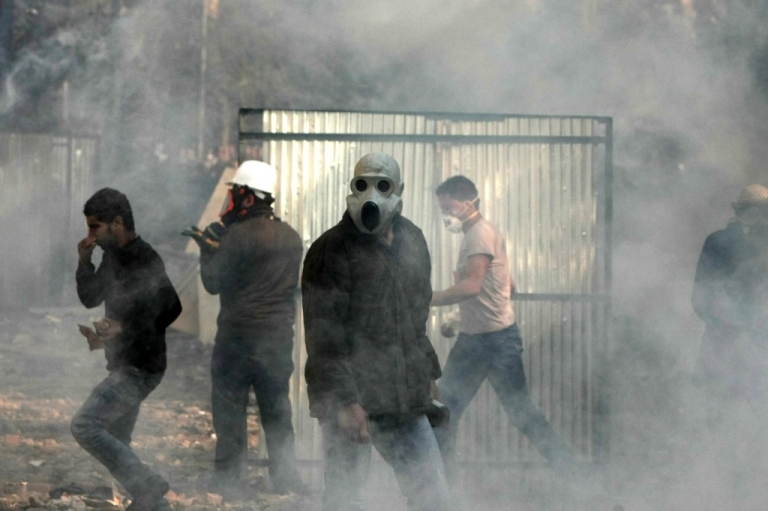 <p>Egyptian protesters wear masks for protection against tear gas during clashes with riot police along a road which leads to the Interior Ministry, near Tahrir Square, in Cairo on November 23, 2011.</p>