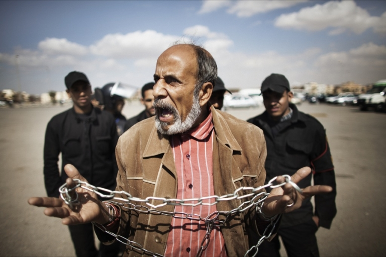 <p>An Egyptian protester holds a chain as he shouts slogans against ousted Egyptian president Hosni Mubarak outside the police academy in Cairo where his trial is drawing to an end on February 16, 2012. The verdict in the trial of Mubarak will be announced on February 22, presiding judge Ahmed Refaat said.</p>