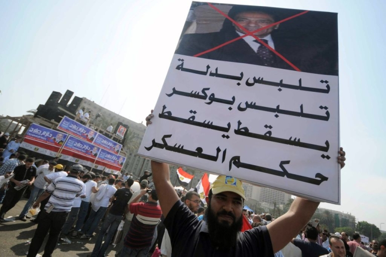 <p>An Egyptian protester holds a banner against Field Marshal Hussein Tantawi in Cairo's Tahrir Square on September 30, 2011 during a mass rally to reclaim the revolution amid anger over the military rulers' handling of the transition.</p>