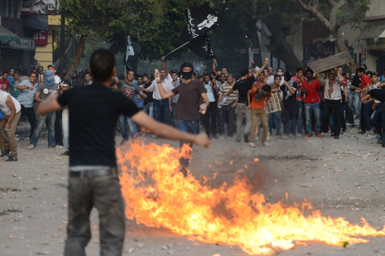 <p>Opponents of the Muslim Brotherhood and President Mohamed Morsi (back) throw Molotov cocktails towards government supporters during clashes in Tahrir Square in Cairo on October 12, 2012.</p>