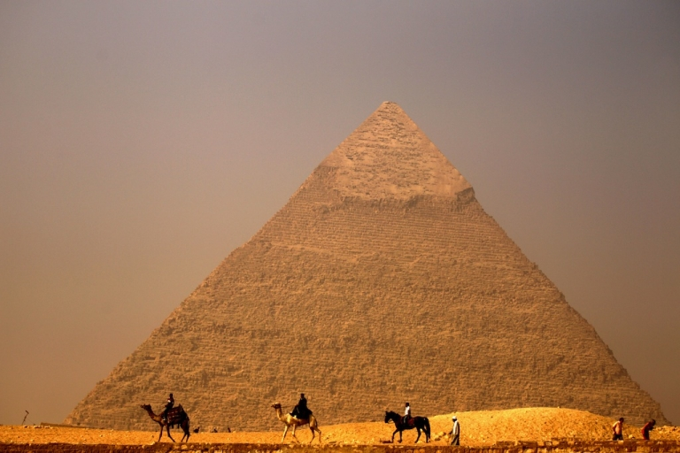 <p>Egyptians ride their camels past the pyramid of Khafre in Giza, on the outskirts of Cairo, on November 30, 2010.</p>