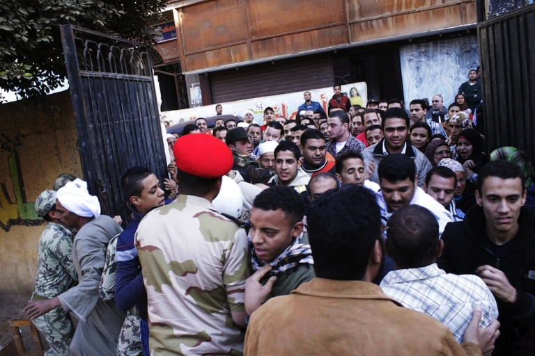 <p>Egyptian voters scuffle with army soldiers as they enter a polling station in Giza, south of Cairo, on December 22, 2012. Egyptians voted in the final round of a referendum on a new constitution championed by President Mohamed Morsi and his Islamist allies, but with little prospect of the result quelling fierce protests.</p>