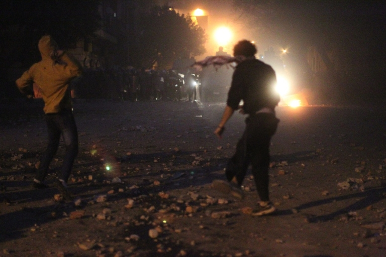 <p>Egyptian protesters throw stones during clashes with riot police at Cairo's landmark Tahrir Square on November 19, 2011, as Egyptian police fired rubber bullets and tear gas to break up a sit-in among whose organisers were people injured during the Arab Spring which overthrew veteran president Hosni Mubarak.</p>