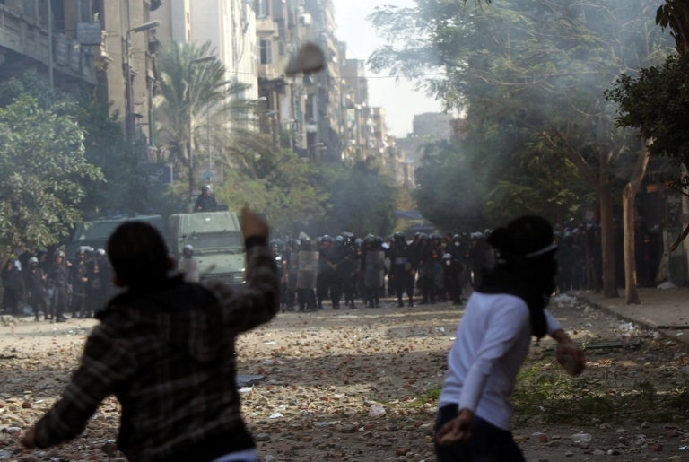 <p>Egyptian protesters lob stones as they face off against riot police during clashes at Cairo's Tahrir Square on November 20, 2011.</p>