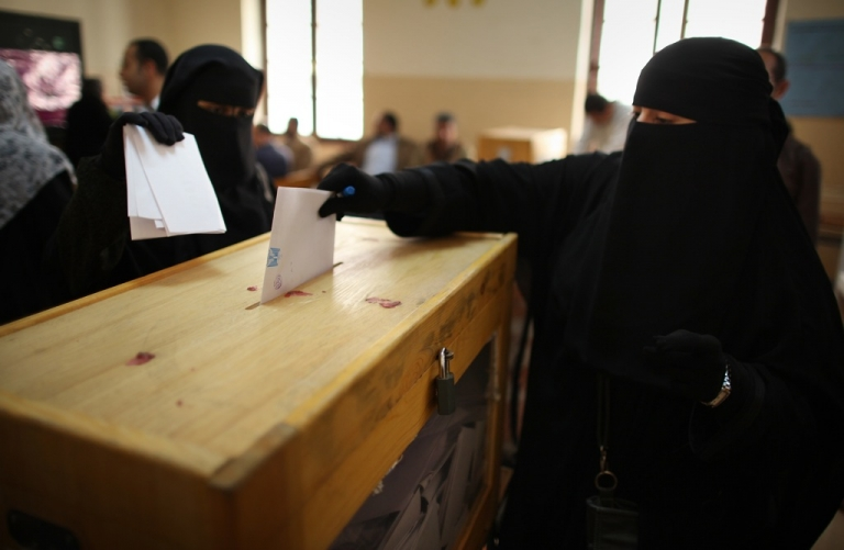 <p>Women place their votes in a ballot box at a polling station in a girls school on November 28, 2011 in Downtown Cairo, Egypt.</p>