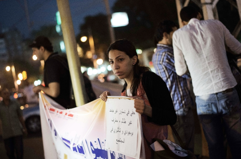 <p>An Egyptian woman holds a slogan which reads in Arabic 'My right in the Constitution is ungrateful and unjust, I recognize my presence and effect in the community' during a demonstration in front of the presidential palace in Cairo on October 4, 2012, to support women rights in the constitution and protest against child marriage.</p>