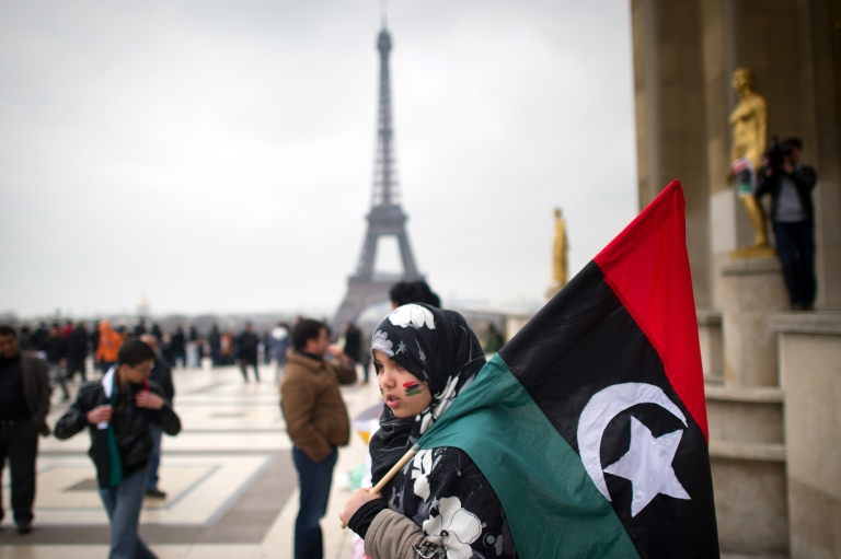 <p>A woman holds a Libyan monarchist flag, dated from before the iron-fisted rule of Muammar Gaddafi, during a demonstration to protest against attacks by Colonel Kadhafi's planes on the people of Benghazi, on the Trocadero square in front of the Eiffel Tower, on March 19, 2011 in Paris.</p>