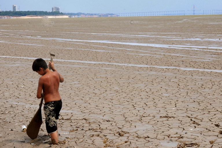 <p>El Nino cometh: A boy plays with a paddle on the dried bed of the Negro river in northern Brazil in October 2010, when the El Nino climate phenomenon struck. It's a complicated phenomenon that hits different regions in different ways.</p>