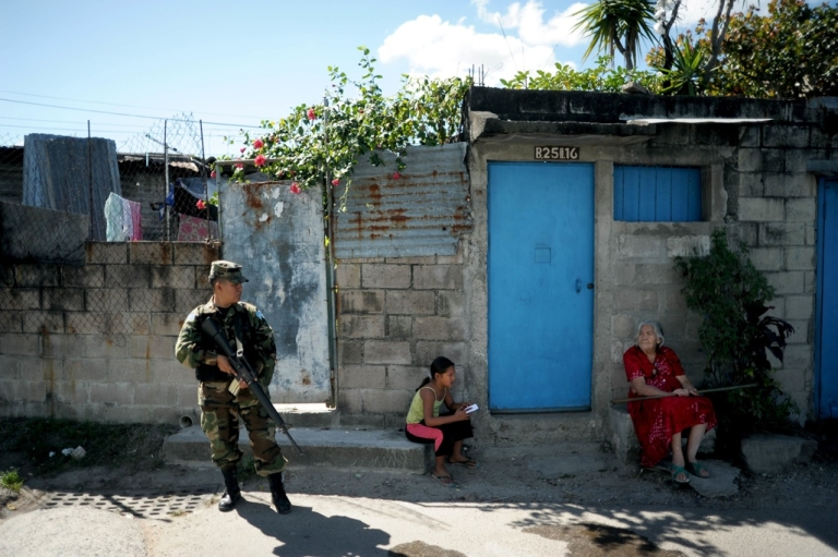 <p>A Salvadoran soldier stands guard in a San Salvador slum where gang violence had been escalating. A truce between the country's chief rival gangs is expected to stem the violence but many Salvadorans are skeptical it will hold.</p>