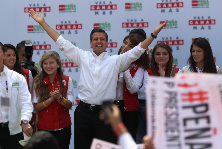 <p>Front-runner Enrique Pena Nieto stands with his family while greeting supporters at his final campaign rally on June 24, 2012 in Mexico City.</p>