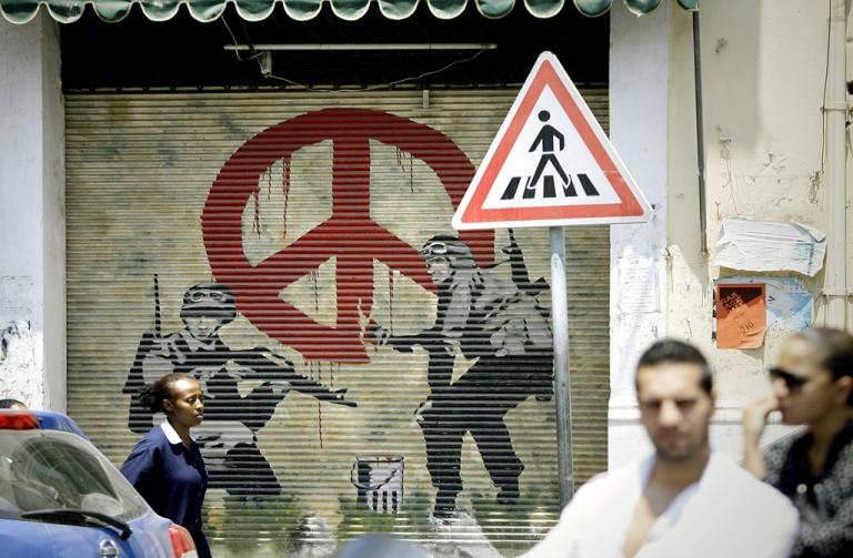 <p>An Ethiopian woman walks past a shuttered shop decorated with images of two solider and the 'Love and Peace' sign in the Christian neighbourhood of Jemmayzeh in Beirut on July 11, 2012.</p>