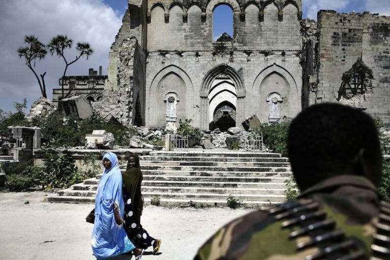 <p>Somali women walk in front of an Ethiopian soldier in Mogadishu on Dec. 8, 2007.</p>