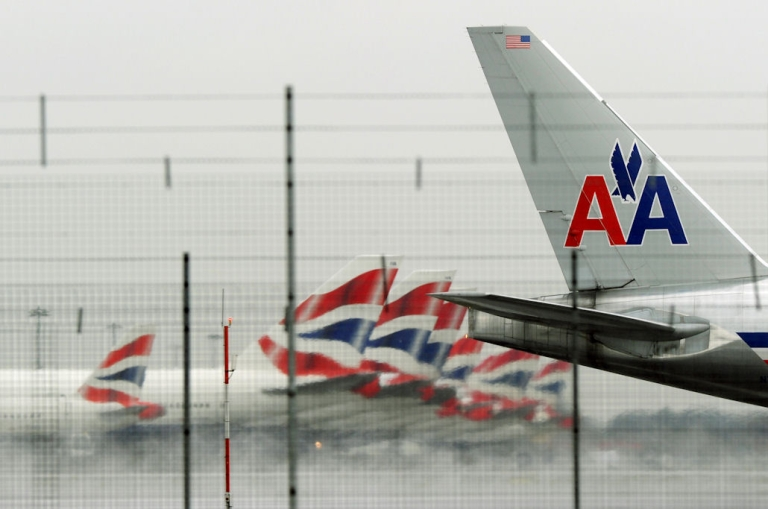 <p>An American Airlines jet speeds past British Airways planes parked at Terminal 5 during takeoff from London Heathrow Airport on March 25, 2010.</p>