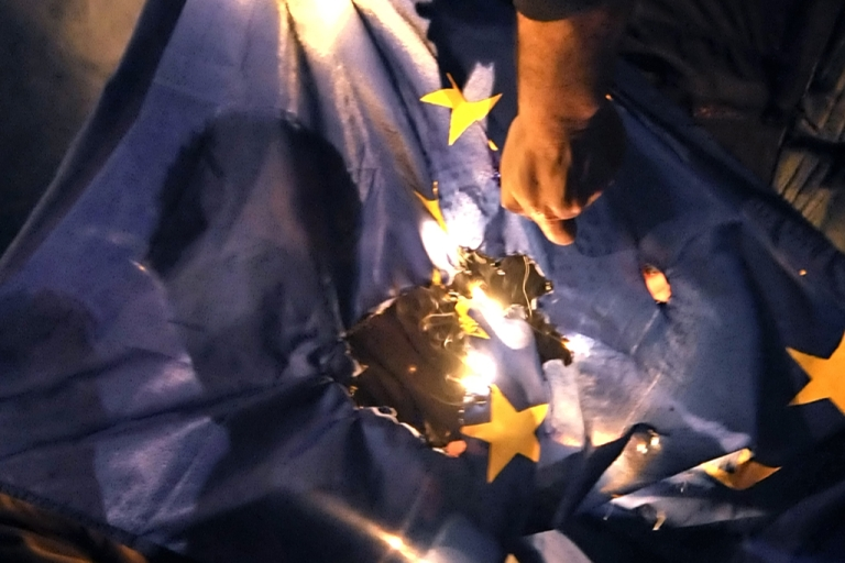 <p>Demonstrators burn an EU flag near the EU offices in Athens during a protest against harsh austerity measures.</p>