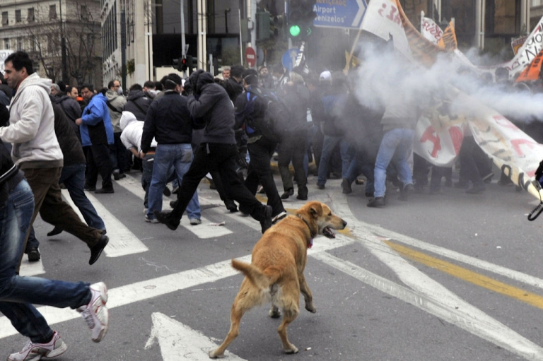 <p>Protesters run from tear gas during clashes which broke out at a march in Athens on Feb. 23, 2011. Greece was hit with a general strike against government austerity measures as Prime Minister George Papandreou seeks to convince the cash-strapped country's euro zone partners to extend the repayment of a massive rescue loan.</p>
