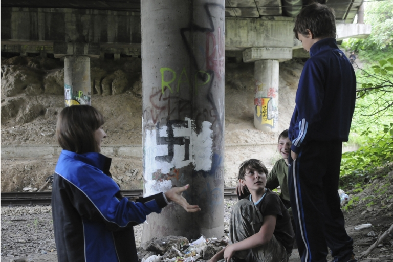 <p>Children play near a bridge column with Nazi graffiti in Lviv, Ukraine, on May 30, 2012. Euro 2012 organizers refute claims that Poland and Ukraine were unsafe for traveling soccer fans.</p>