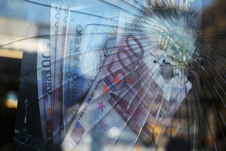 <p>A broken window in front of a poster featuring Euro banknotes in a money transfer shop in Athens, Greece.</p>