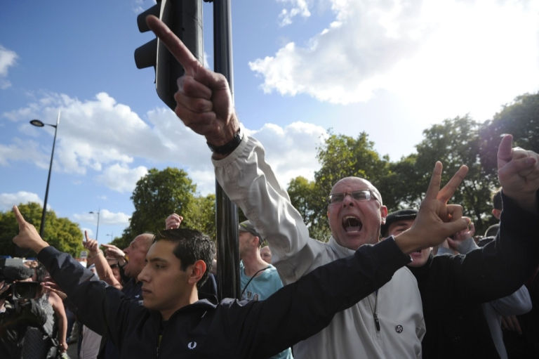 <p>Members of the right-wing English Defence League (EDL) shout at Islamist demonstrators protesting outside the US embassy in London on Sept. 11, 2011 during a ceremony to mark the 10th anniversary of the 9/11 attacks on the United States. Around 50 people brandished anti-US banners, chanted slogans and burnt a small piece of paper with a picture of the US flag on it.</p>