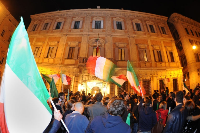 <p>Italian Prime Minister Silvio Berlusconi's supporters wave Italian flags in front of his residence, Palazzo Grazzioli, the day after he resigned on Nov. 13, 2011 in Rome.</p>