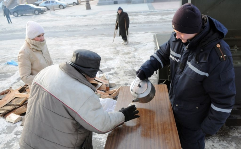 <p>An elderly man receives hot food and drink at an emergency shelter in the western Ukrainian city of Lviv, on January 30, 2012.</p>