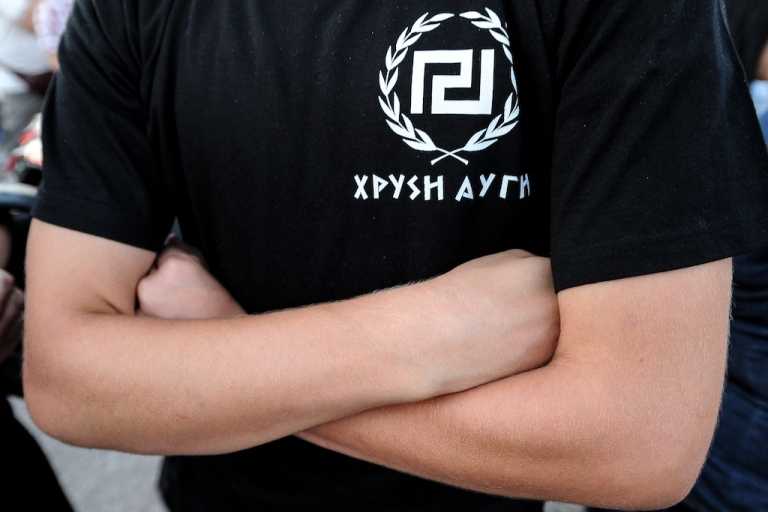 <p>A supporter of extreme-right ultra nationalist party Golden Dawn (Chryssi Avghi), waits during a rally in Athens in June. Many accuse the party of being complicit in vigilante violence and using neo-Nazi, anti-immigrant rhetoric.</p>