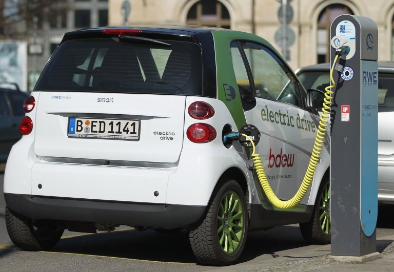 <p>An electric Smart car charges at a public charging station on March 28, 2011 in Berlin, Germany. The city of Berlin has teamed up with several auto companies and energy utilities in an electric car pilot project.</p>