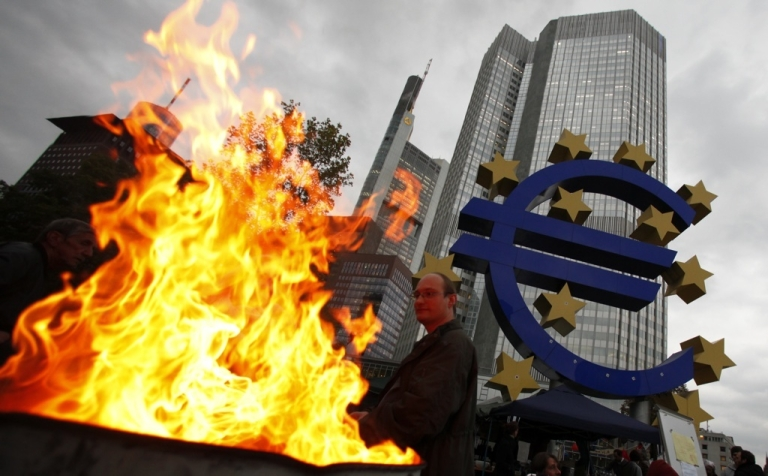 <p>A pedestrian walks in front of the headquarters of the European Central Bank on Oct. 18, 2011 in Frankfurt, Germany. Around hundred protesters operate a camp outside the ECB to demonstrate against economic and financial policy.</p>