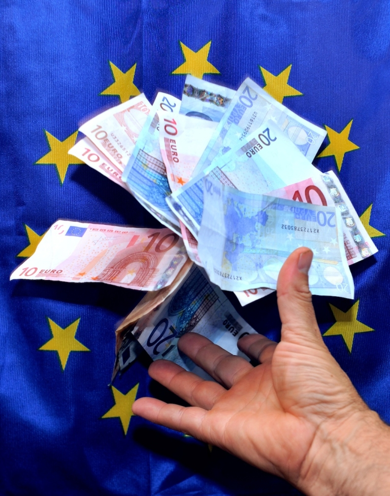 <p>Euro notes are shown against a European Union flag, on August 4, 2012, in Lille, northern France.</p>
