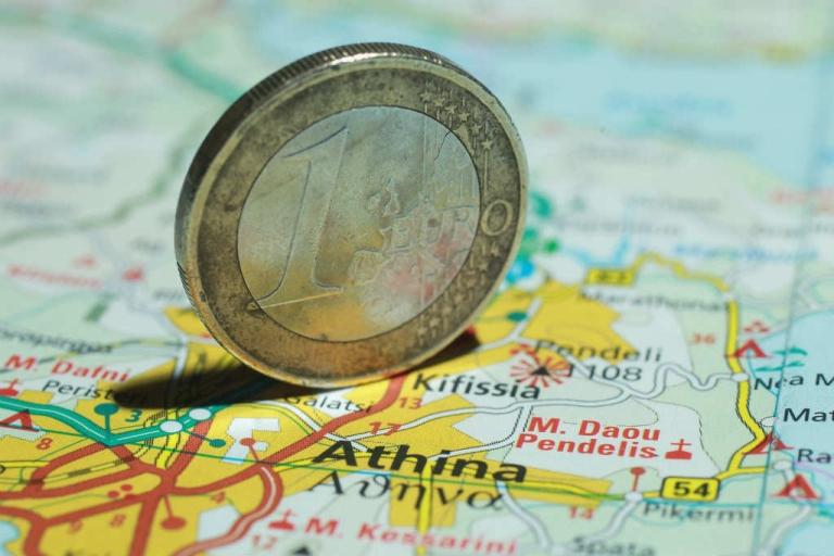 <p>A euro coin stands on a map of Greece. Many fear that a Grexit from the Eurozone would worsen the crisis.</p>
