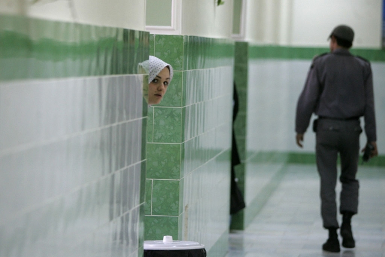 <p>An Iranian inmate peers from behind a wall as a guard patrols the female section of Evin prison in Tehran, Iran, in this 2006 file photo.</p>