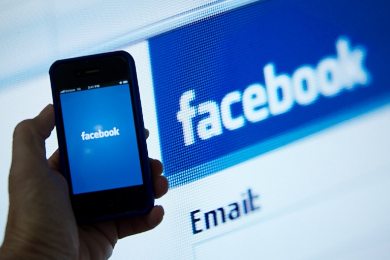 <p>A view of an Apple iPhone displaying Facebook app's splash screen in front of the login page. Social-networking giant Facebook will go public on the NASDAQ May 18 with its initial public offering, trading under the symbol FB, in an effort to raise $10.6 billion.</p>