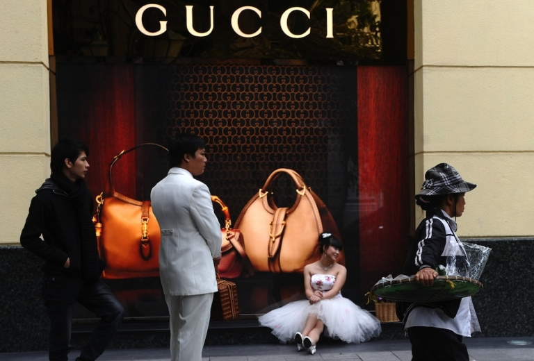<p>A young couple poses for their wedding photos outside a Gucci store in Hanoi on December 6, 2012.</p>