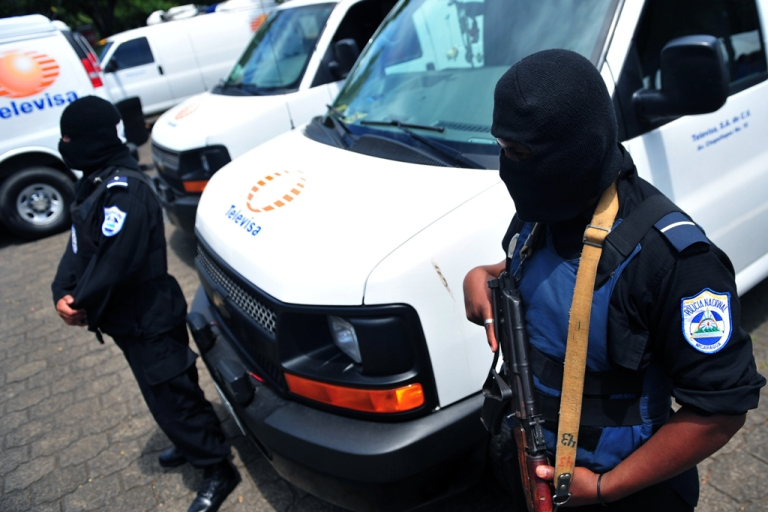 <p>Nicaraguan National Police members stand guard in front of seized vans on August 24, 2012 in Managua, following the arrest of 18 foreigners on August 21, while trying to enter the country as journalists of Mexico's Televisa. Mexico's embassy in Nicaragua had already issued a report stating that Televisa denied the men were part of their firm, and that they carry on with the investigation to confirm the nationality of the detainees. Seven million USD were found inside the vans --in