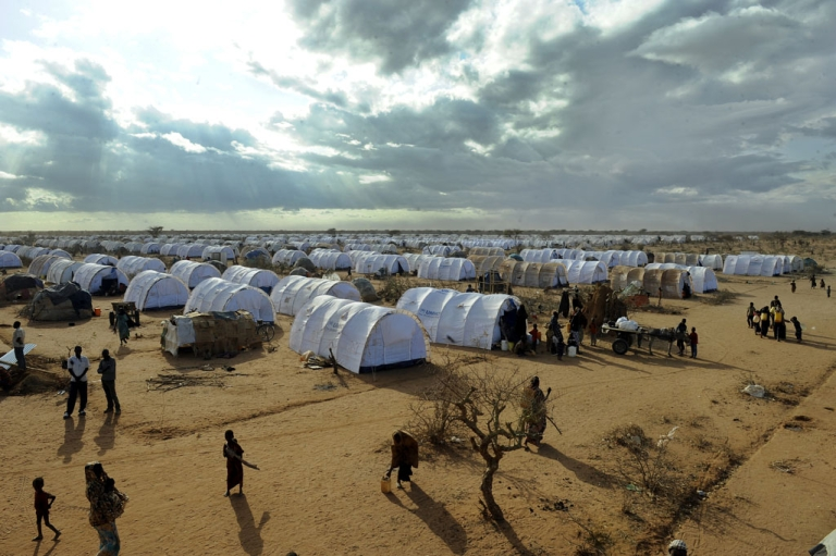 <p>Somali refugees walk by a new extension of the Dadaab camps complex where 1,500 people are arriving everyday fleeing drought and famine.</p>
