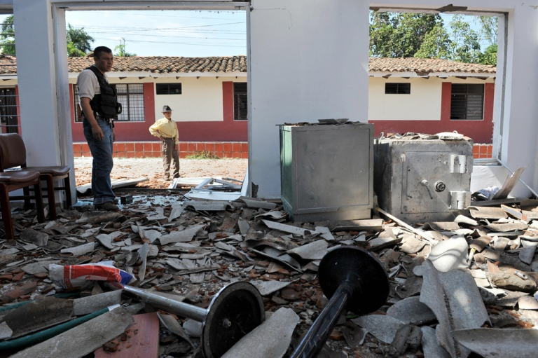 <p>A policeman and a local resident look at the ruins of a Bank office after a bombing attack by the Revolutionary Armed Forces of Colombia (FARC) guerrillas.The FARC are suspected of bombing two police stations in Colombia in the past week.</p>
