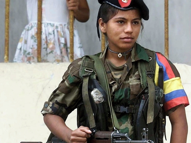 <p>A female FARC fighter stands guard in Los Pozos, on Feb. 8, 2001.</p>