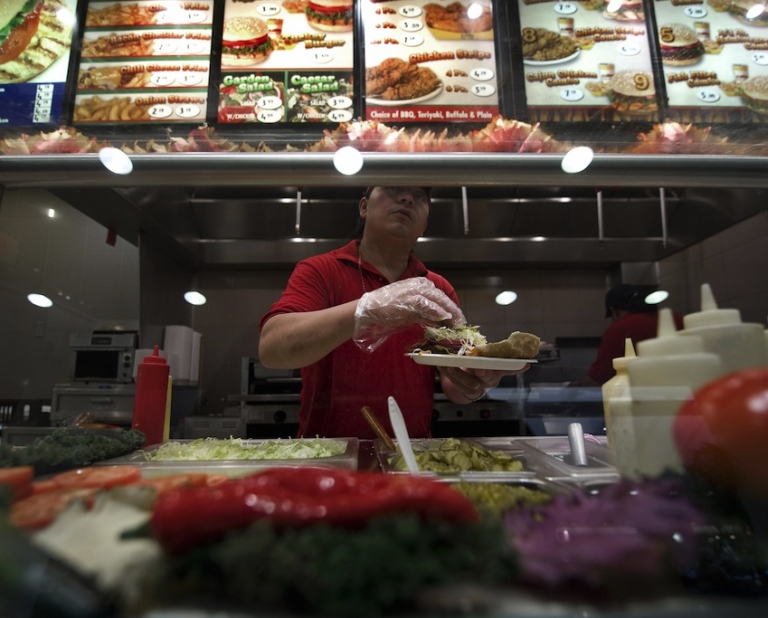 <p>A worker in a fast food restaurant serves up lunch in the food court of the Ronald Reagan Building on November 18, 2008, in Washington, DC.</p>
