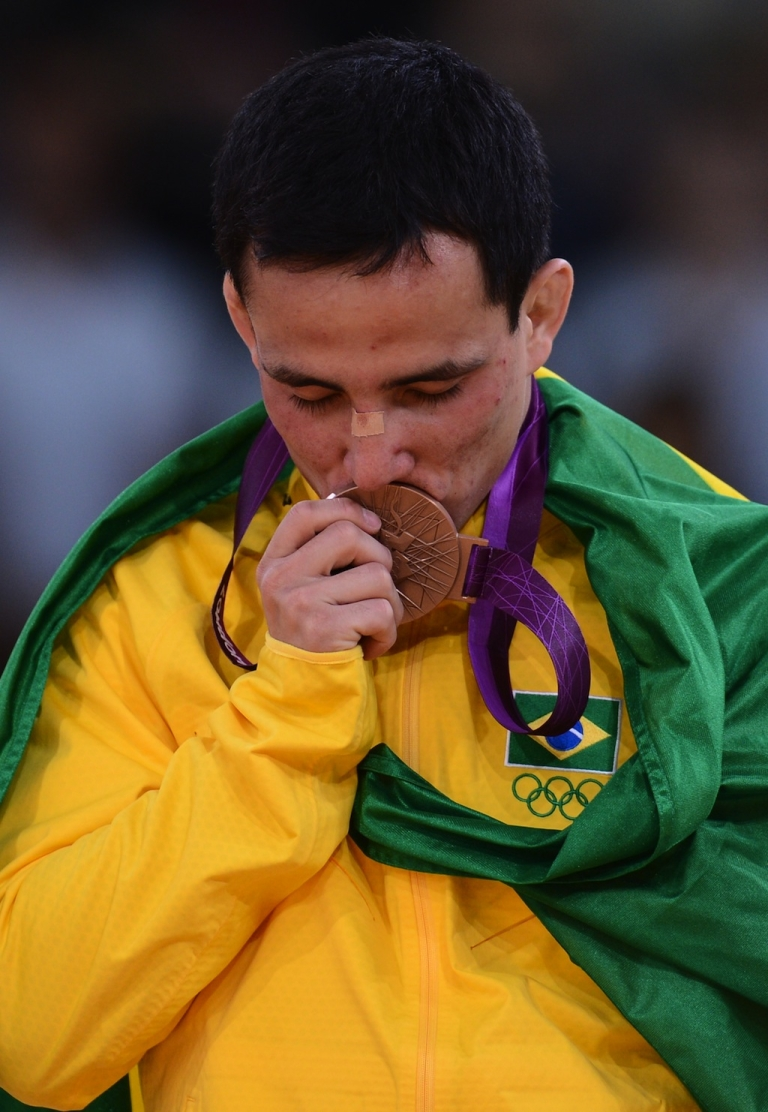 <p>Brazil's Felipe Kitadai with the bronze medal in question, now broken and dented after hitting the shower floor.</p>