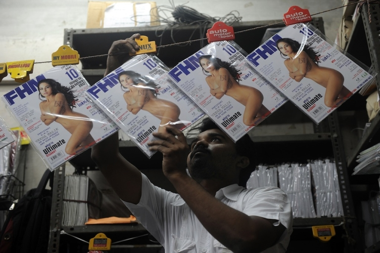 <p>A bookstore employee displays copies of the FHM magazine upon delivery in Mumbai on December 5, 2011. India's version of FHM magazine has defended the cover of its December issue, which shows a nude Pakistani actress with the initials of Pakistan's powerful intelligence agency displayed on her arm. A preview of the cover on the magazine's website triggered a media frenzy which intensified when actress Veena Malik denied posing nude and accused FHM of doctoring her image.</p>