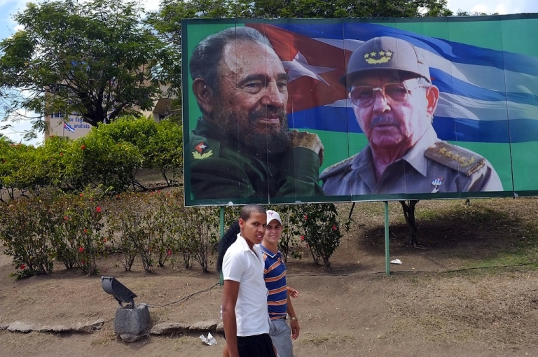 <p>Two teenagers walk past a billboard of Fidel and Raul Castro.</p>