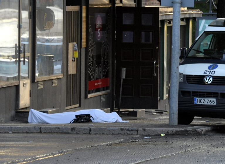 <p>The body of a shooting victim lies covered with a sheet as Police cordon off the area following multiple shootings by a gunman in Hyvinkaa, Finland, May 26, 2012.</p>